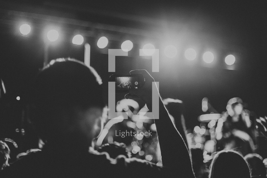 taking a picture with a cellphone at a concert