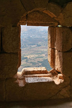 view of a hillside through a window in ruins in Jordan