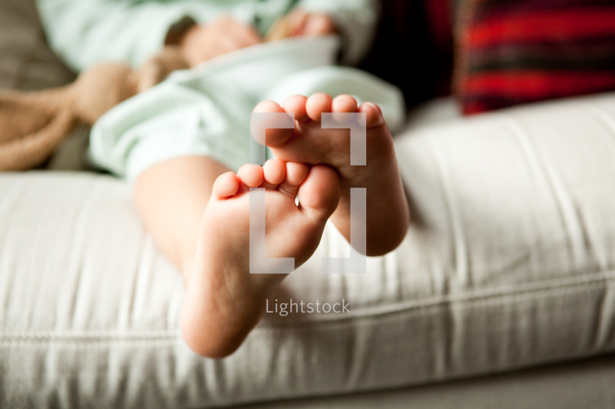 toddlers bare feet sitting on a couch