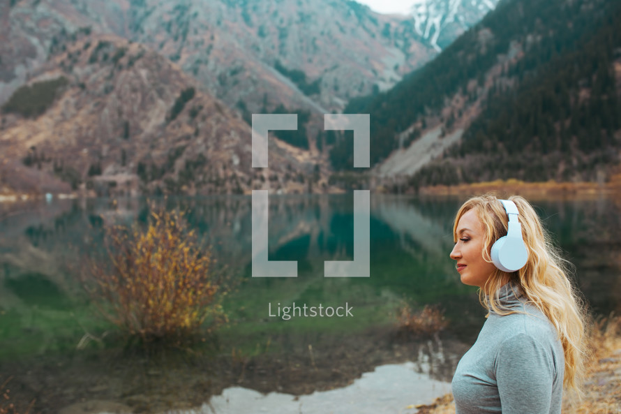 woman listening to headphone with a lake shore