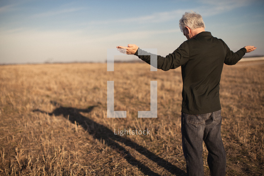 elderly man standing outdoors in a field with his arms outstretched in praise and worship to God