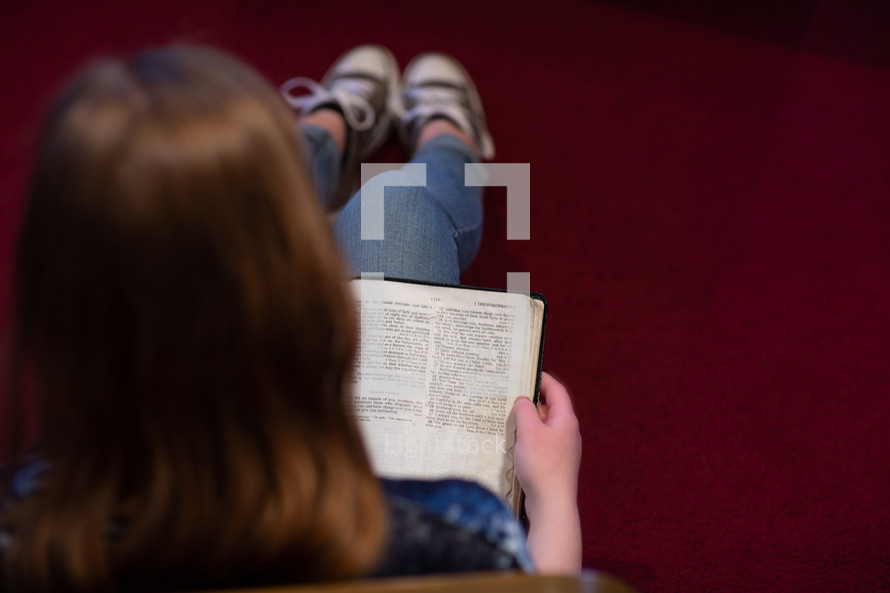 View over shoulder of a young woman or teen sitting on floor of a church meditating on scripture, I Thessalonians 5 - Christian conduct.
