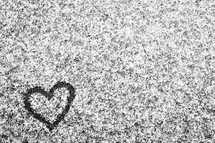 heart drawn in the snow on pavement