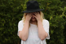 a woman hiding her face
