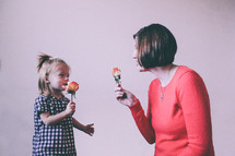 Mother and daughter holding roses.