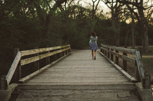 woman walking across a wooden footbridge
