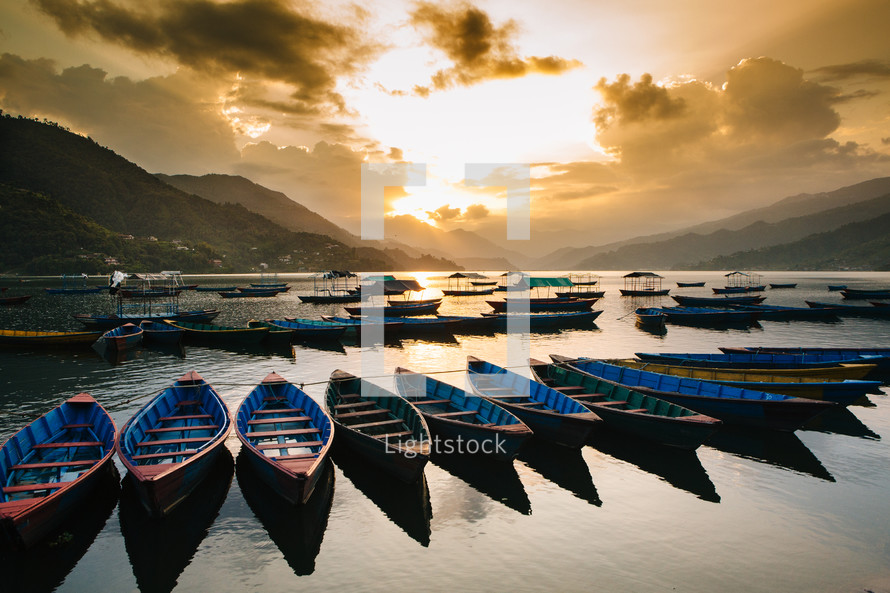 boats anchored in a harbor at sunrise