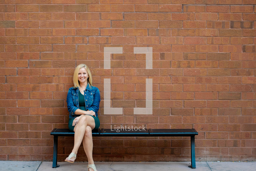 a smiling woman sitting on a bench