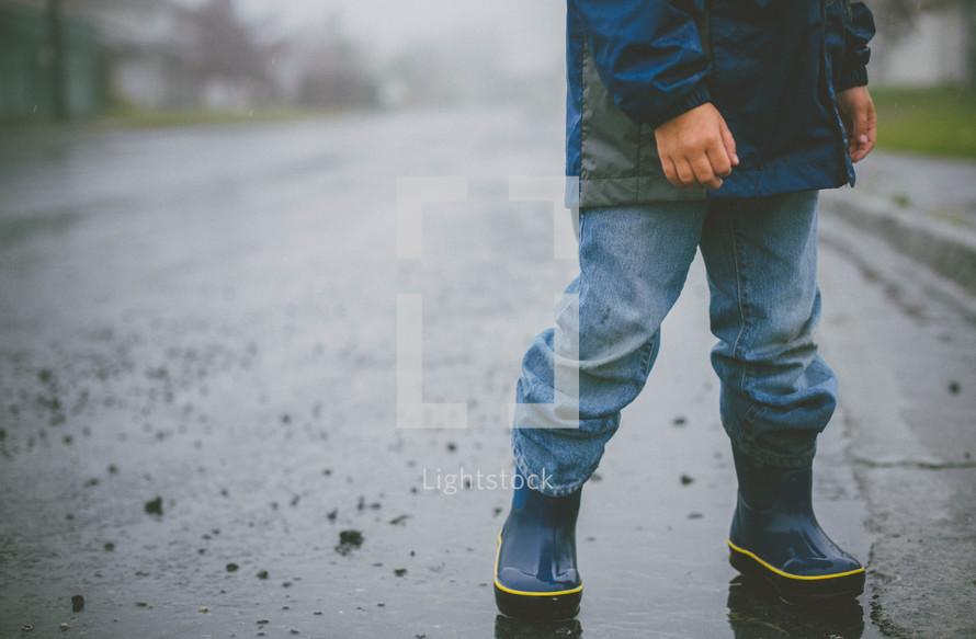 Child in rain boots crossing the wet street.