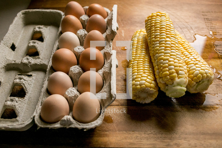 Eggs in a carton and corn on the cob on a wet cutting board.