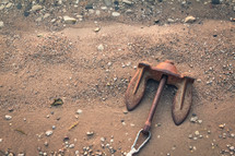 rusty anchor lying on the shore