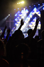 silhouettes of raised hands at a worship service
