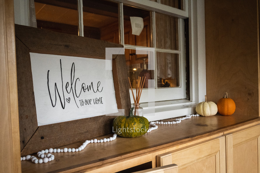 Welcome to our home sign and pumpkins