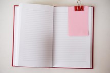 open journal, clip, and pink paper