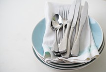 silverware and napkins on stacked plates