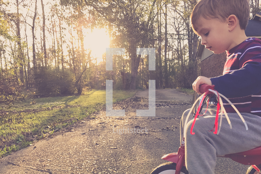 toddler riding a tricycle at sunset