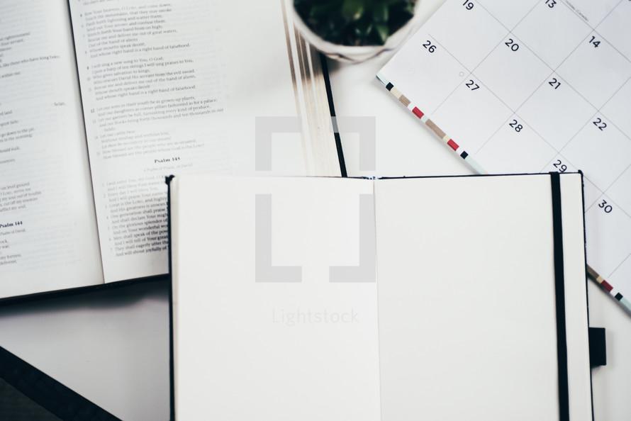 open Bible, journal, and calendar on a desk