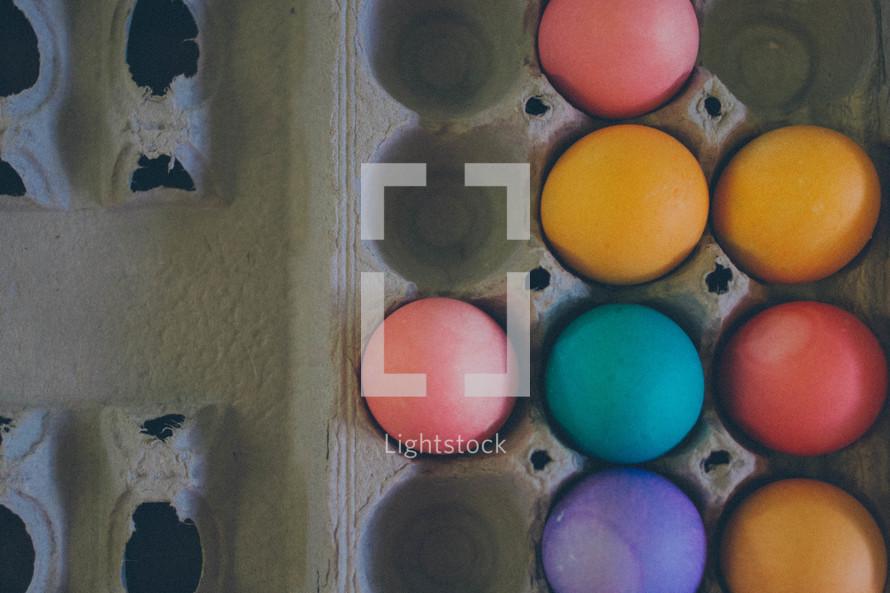 colored eggs in a carton