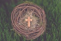 A wooden cross in a bird's nest