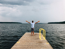a man on a dock with arms outstretched