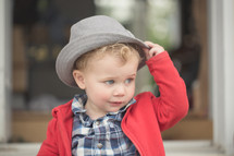 A little boy in a red coat and gray hat.