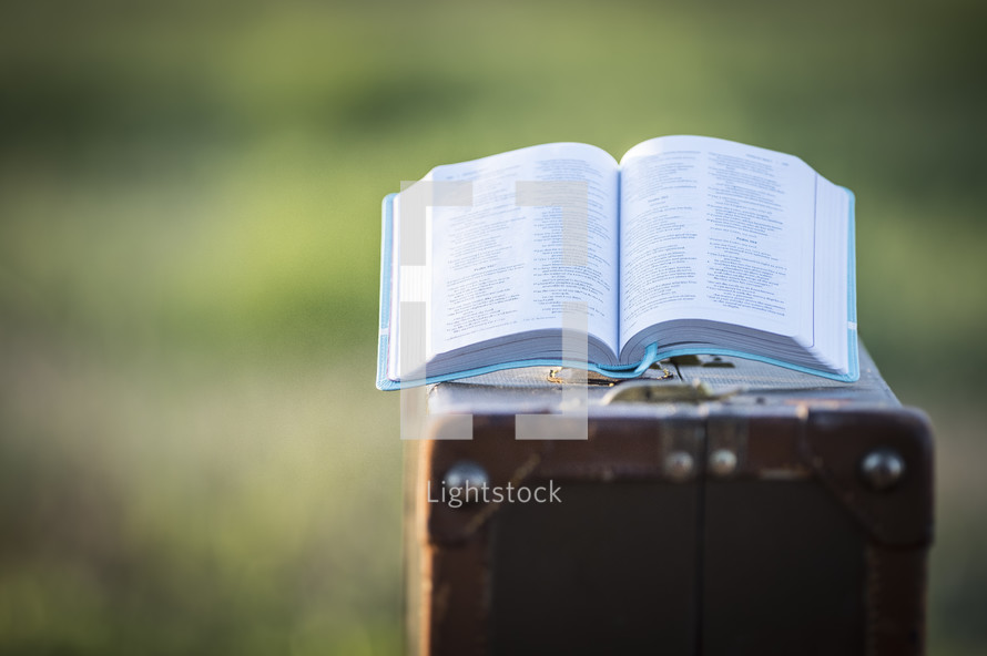 open Bible on a suitcase