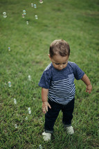 a toddler boy chasing bubbles in the grass
