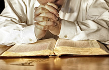 A married man in a white, long-sleeved shirt bows his head and has his hands clasped in deep prayer over his Holy Bible. (Model release on file)