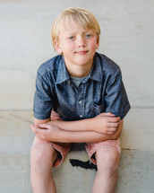 portrait of a young boy sitting on a curb