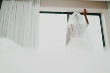 a bride standing in a window praying