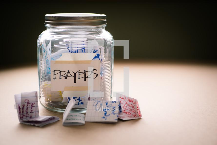 "A glass jar labeled ""prayers"" full of handwritten notes."