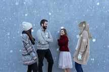 friends standing outdoors talking in the snow
