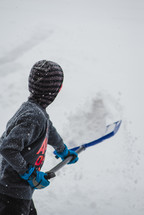 child digging with a shovel in snow