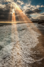 rays of sunlight shining down on a shore