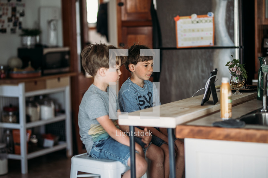 two boys doing a video conference in a kitchen