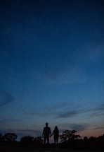 A couple holding hands at dusk
