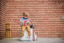a child reading a book sitting on a locker