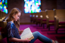 Young woman or teen sitting in aisle of a church meditating on scripture.