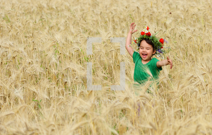 happy girl playing in wheat field