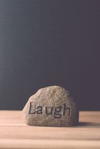 a rock with the word laugh