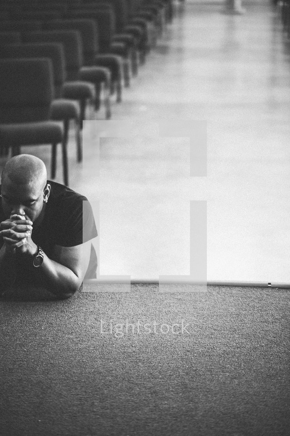 Man leaning on stage with eyes closed in prayer.