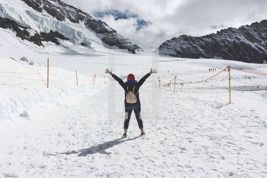 a woman with raised hands standing on a snowy mountain