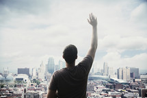 man standing in front of a city with hand raises