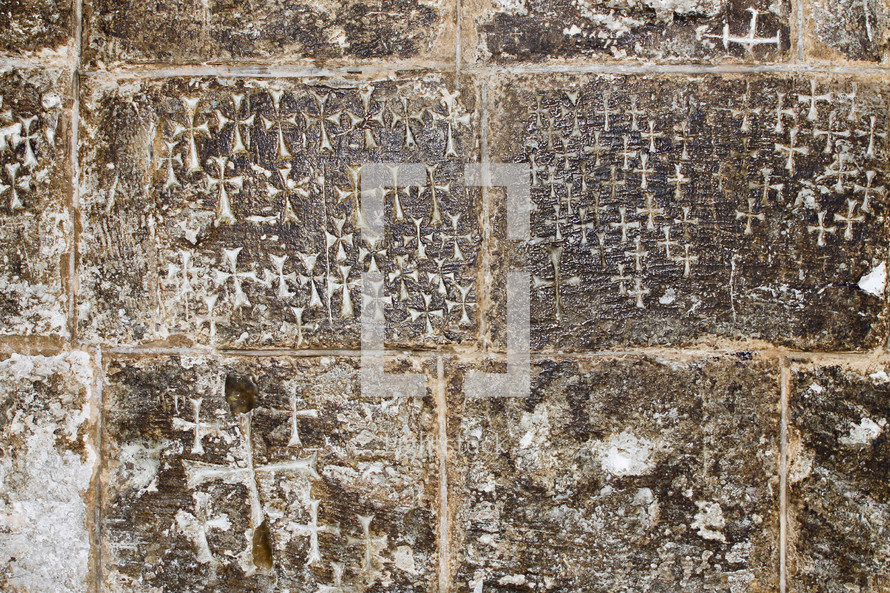 Crosses etched into the stone wall inside of the Church of the Holy Sepulchre.