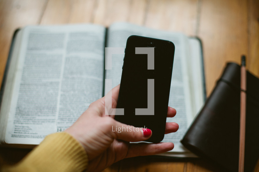 open Bible, cellphone, and journal