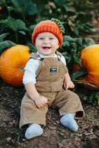 toddler in overhauls with a pumpkin