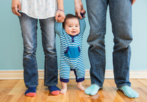 Infant child standing on the wood floor holding his parents' hands.