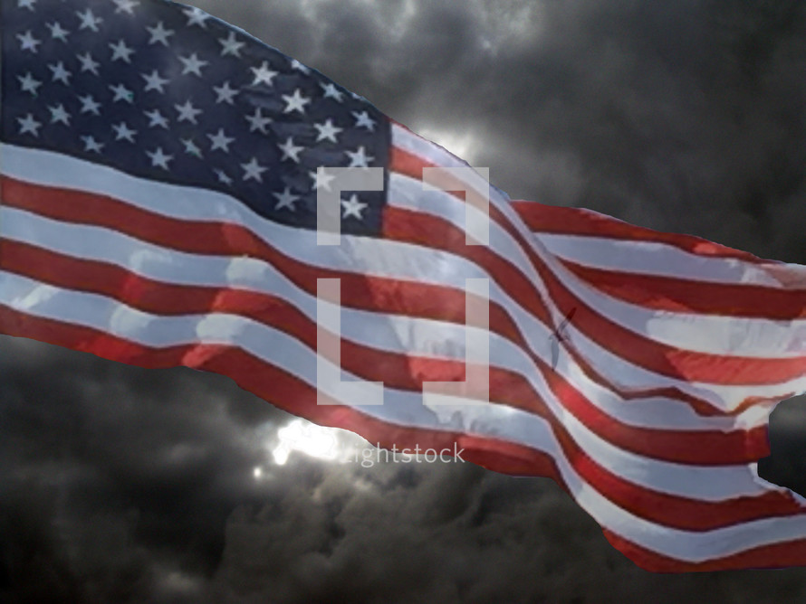 The Stars and Stripes of the American Flag wave in the wind against a stormy dark cloudy sky symbolizing coming tribulation, storms and troubled times as the world turns from God more and more preparing the world for the rapture, the Anti-Christ and the years of tribulation before Christ's return.