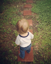 toddler boy standing on stepping stones