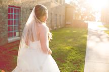 a bride walking outdoors under bright sunlight